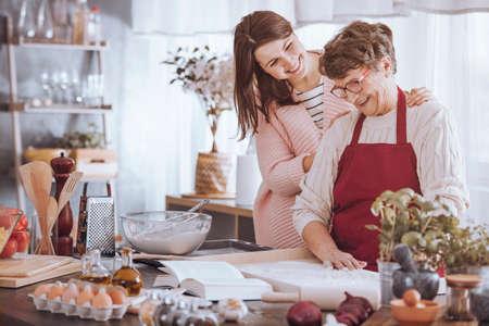 台所でケーキを作っている間に祖母の肩をマッサージする笑顔の女性