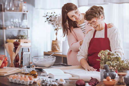 Smiling woman massaging grandmother's shoulder while making cake in the kitchen