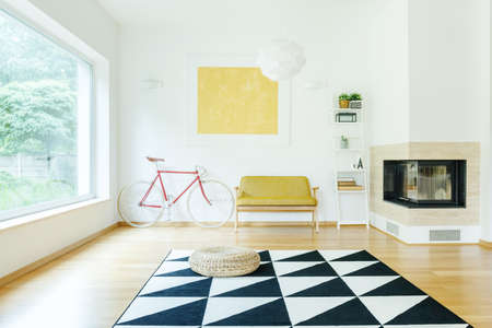 Pouf on triangle carpet in bright living room with fireplace yellow sofa and red bike against wall with gold painting Stock Photo