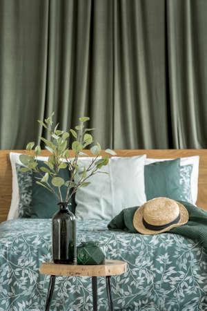 ベッドの後ろにカーキ色の布が付いている寝室の小さなテーブルに置かれた花瓶の形をしたボトルで、葉と小枝