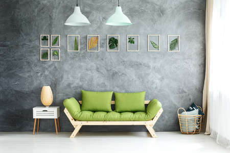 Set of framed tropical leaves and pastel lamps hanging above green wooden sofa, white cupboard and wicker basket with pillows Stockfoto
