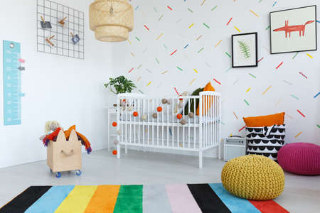 Colorful carpet in bright kids bedroom with wooden box and yellow and pink pouf near cradle