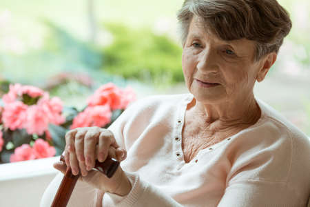Elder woman sitting on white sofa with walking cane in room with pink flowers