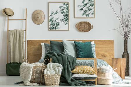 Coussin noeud blanc fait à la main dans le panier en osier debout près du lit avec une literie florale dans une pièce lumineuse avec des chapeaux sur le mur