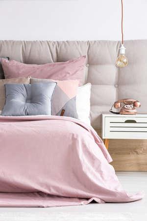 구리 전화 및 전구가있는 현대적인 침실 인테리어의 부드러운 핑크 장식과 장식용 파스텔 쿠션이있는 편안한 침대 스톡 콘텐츠