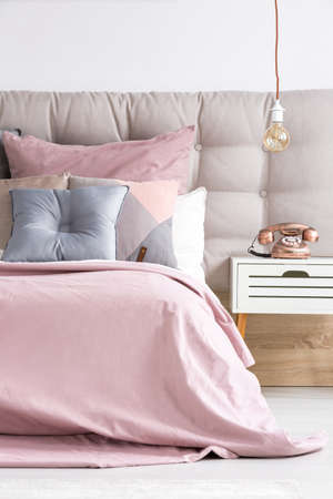 Comfortable bed with soft pink coverlet and decorative pastel cushions in modern bedroom interior with copper phone and light bulb Stok Fotoğraf