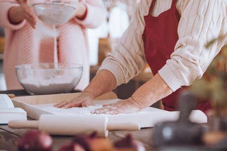 麺棒でカウンターに木の板にケーキを作る人のクローズ アップ