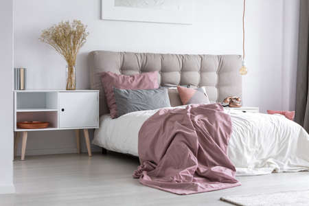 Gray tufted headboard and pink bedcover in simple bedroom with minimalist interior design and copper accessories