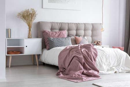 Grijs getuft hoofdeinde en roze bedovertrek in eenvoudige slaapkamer met minimalistisch interieur en koperen accessoires Stockfoto