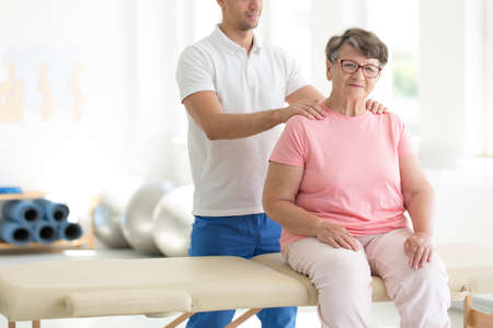 Personal masseur massaging senior woman sitting on massage bed in rehabilitation room Stock Photo