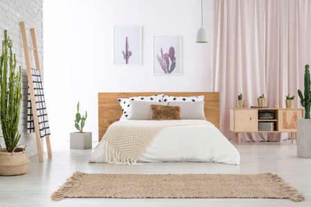 Beige carpet in front of king-size bed near ladder and cupboard in spacious bedroom with cactus motif Foto de archivo