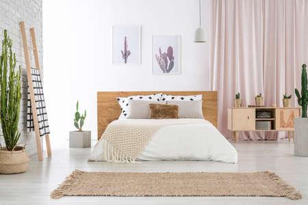 Tapis beige devant un lit king-size près d'une échelle et d'un placard dans une chambre spacieuse avec motif cactus Banque d'images