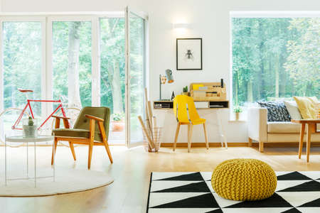 Yellow pouf on geometric carpet in open space interior with green and yellow chair