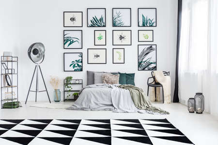 Posters on white wall above king-size bed in white bedroom with geometric carpet,metal lamp and blanket on chair