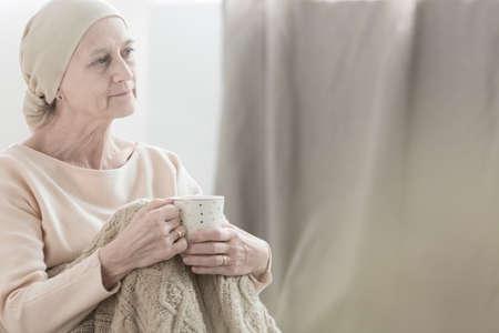 Frau mit dem Tumor friedlich schauen, der ein Kopftuch trägt und eine Tasse Tee hält Standard-Bild - 88996347