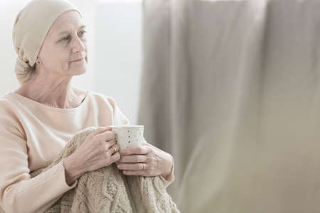 Peacefully looking woman with tumor wearing a headscarf and holding a cup of tea