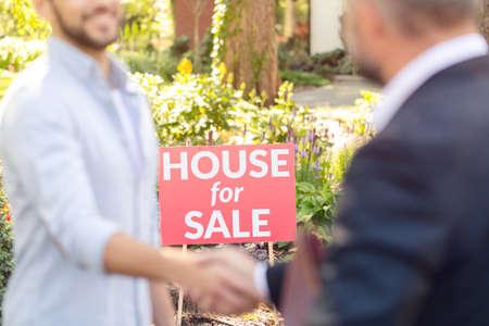 Placa roja con la inscripción de la casa en venta en medio de una transacción