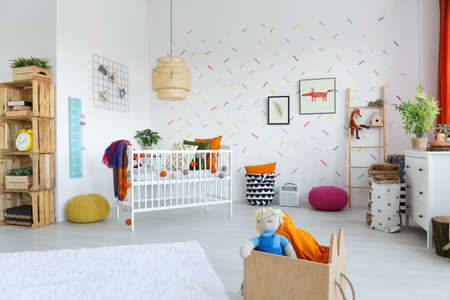 Rattan lamp above white bed with colorful blanket in childs bedroom interior with wooden shelf
