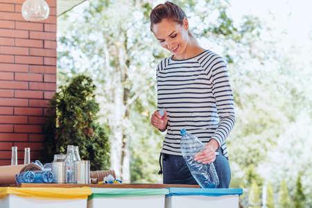 庭で特別なリサイクル容器にプラスチック製のボトルを入れて満足して活動家女性