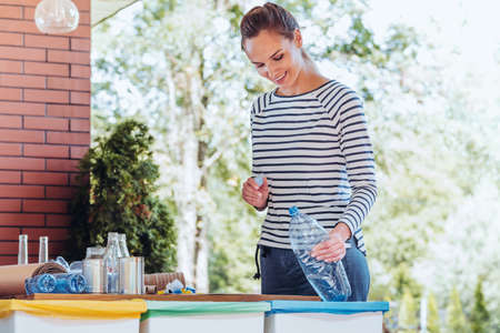 Satisfied activist woman putting a plastic bottle into special recycling container in the garden