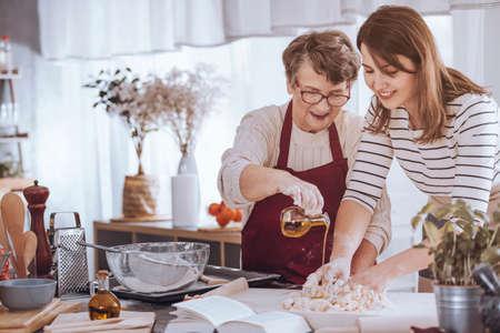 Grootmoeder helpt haar kleindochter deeg te maken door olijfolie toe te voegen Stockfoto - 88987048