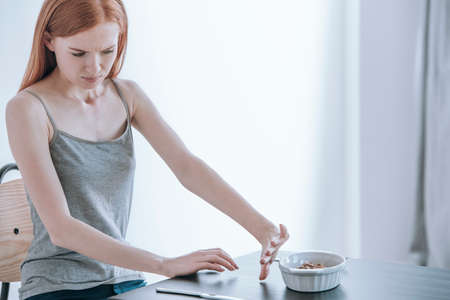 Young depressed girl at table with food in bowl. Eating disorders concept