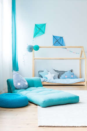 Blue pouf next to mattress in boys bedroom with handmade kites above wooden bed with blue pillows