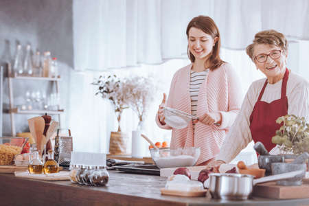 Senior woman smiling while granddaughter sifting flour in the kitchen Stockfoto