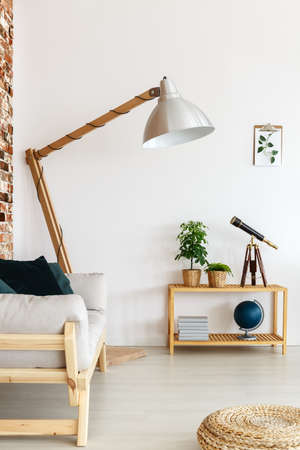 Large floor lamp and wooden sofa in bright interior of contemporary living room with globe, plants and telescope on small console table