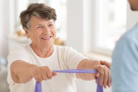 Smiling senior woman doing strength exercise with elastic band during fitness class