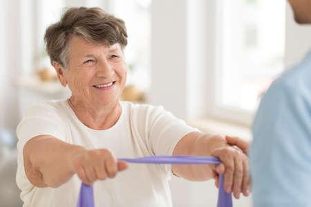 Uśmiechnięta starsza kobieta robi siły ćwiczeniu z elastycznym zespołem podczas sprawności fizycznej klasy