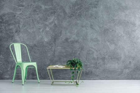 Silla de menta al lado de la mesa con el libro y la planta contra la pared con textura gris en la habitación espaciosa, copia espacio interior concepto Foto de archivo - 88997182