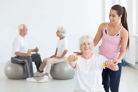 Happy grandma exercising with dumbbells at the gym with the help of young personal trainer