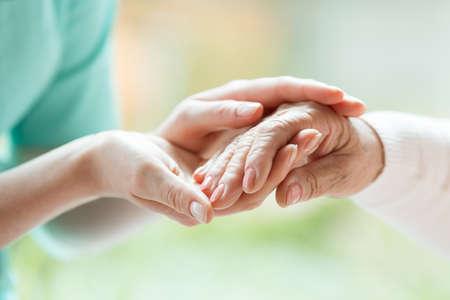 Senior persoon die de verpleegster voor haar hulp tijdens een vergadering in een verpleeghuis dankt
