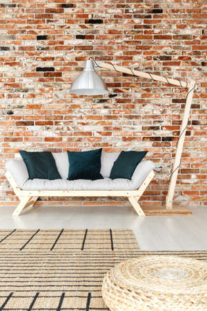 Living room in raw style loft interior with brick wall and large lamp next to wooden sofa with dark green cushions