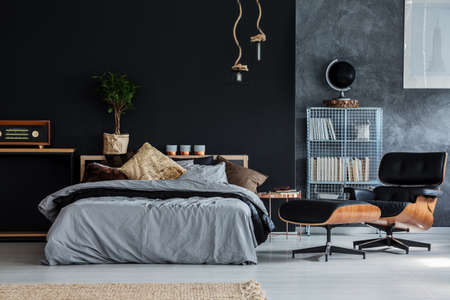 Gold pillow on bed in dark guy bedroom with chaise lounge and vintage radio Standard-Bild