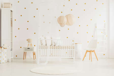 Wooden crib with canopy and pillows in white baby room with dotted wall and lanterns