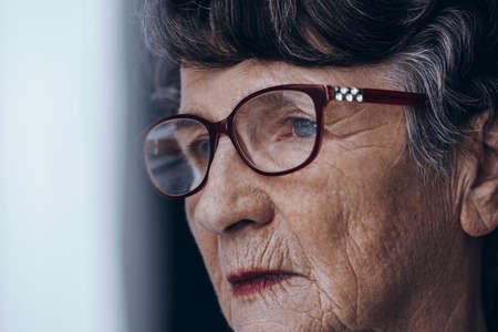 Close-up of sad senior womans face with wrinkles and glasses Stock fotó