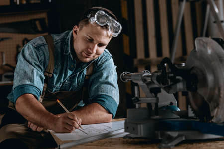 Smiling skilled woodworker sitting at table in protective glasses drawing his new project in the workshop