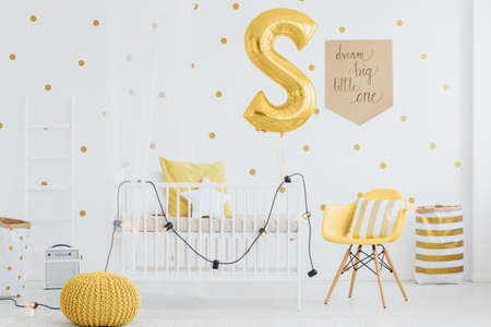 Small lamps hanging on wooden baby bed in room with yellow accents Stock Photo