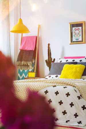 Mexican sugar poster in gold frame above king-size bed with yellow pillow in unique bedroom Stock Photo