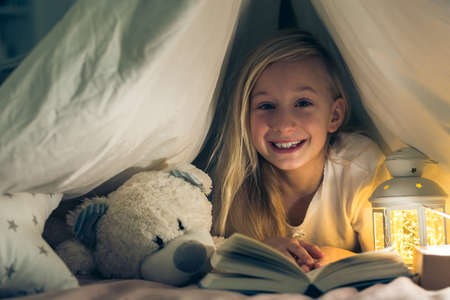 Little girl lying in bed with a book and smiling