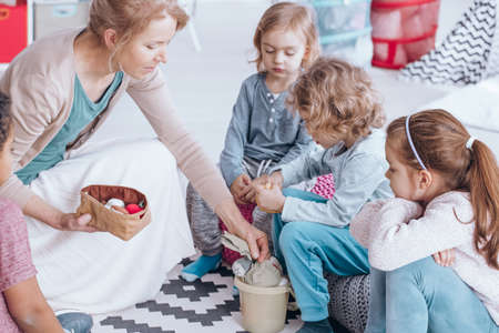 Teacher giving toys to a group of children during activities that develop imagination