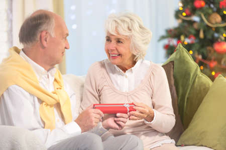 Senior husband gives his wife little red box as a gift