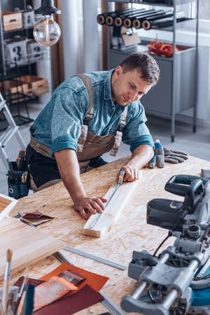 Modern carpenter measuring wooden plank with tape sitting at DIY table in his workshop