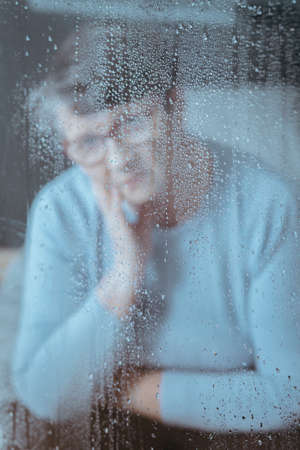 Photo through the window with raindrops with sad grandmother in background