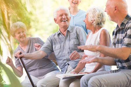 時間公園で一緒に座って過ごすシニアの友達に笑顔のグループ