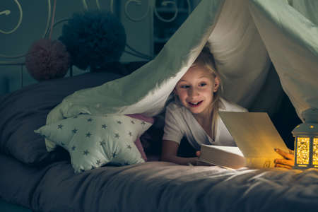 Girl opening a book lying in bed in the dark