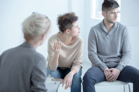 Wife arguing with her husband during marriage therapy with couple therapist