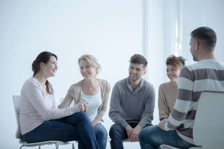 Smiling girl talking about her fight against addiction during meeting with support group Stock Photo